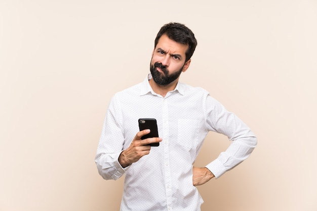 Young man with beard holding a mobile angry Premium Photo