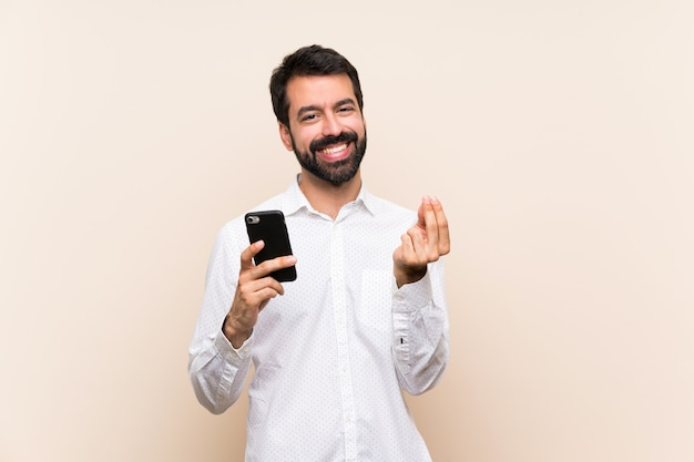 Young man with beard holding a mobile making money gesture Premium Photo
