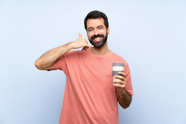 Young man with beard holding a take away coffee over isolated blue  making phone gesture Premium Photo