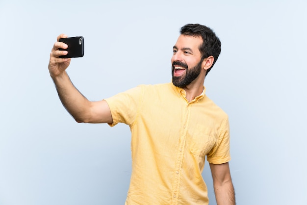 Young man with beard over isolated blue   making a selfie Premium Photo