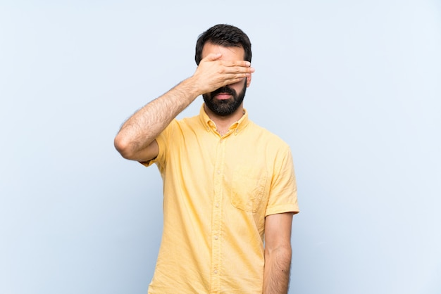 Young man with beard over isolated blue wall covering eyes by hands. do not want to see something Premium Photo