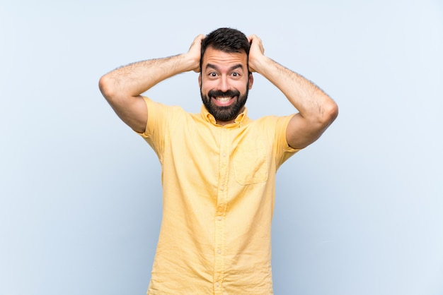 Young man with beard over isolated blue wall frustrated and takes hands on head Premium Photo