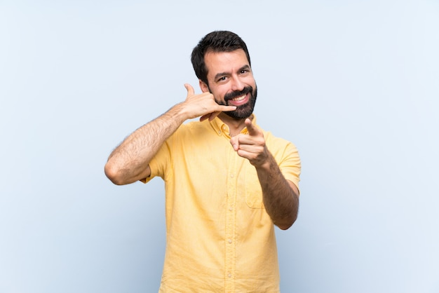 Young man with beard over isolated blue wall making phone gesture and pointing front Premium Photo