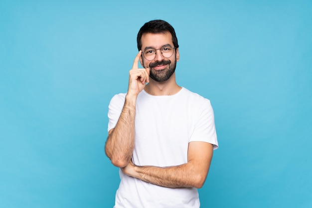 Young man with beard  over isolated blue wall with glasses and happy Premium Photo