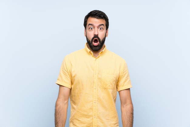 Young man with beard over isolated blue wall with surprise facial expression Premium Photo