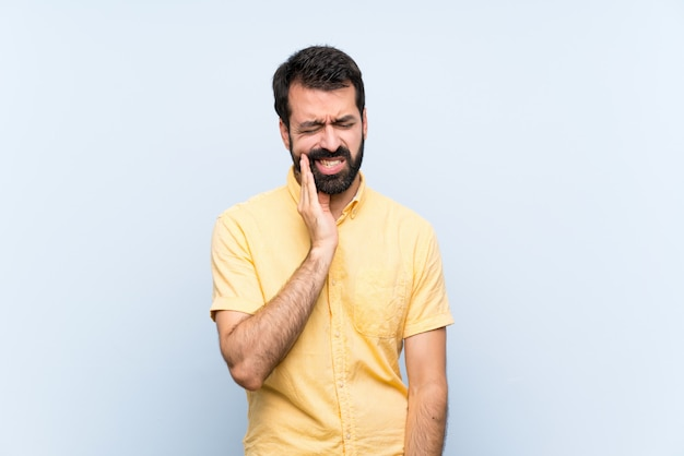 Young man with beard over isolated blue   with toothache Premium Photo