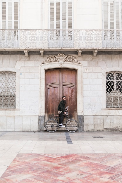 Young man with bicycle standing in front of vintage building Free Photo