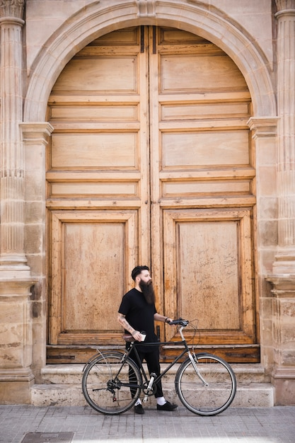 Young man with bicycle standing near the closed vintage door Free Photo