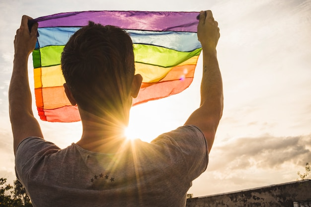 Young man with big flag in lgbt colors and sky with sunshine Premium Photo