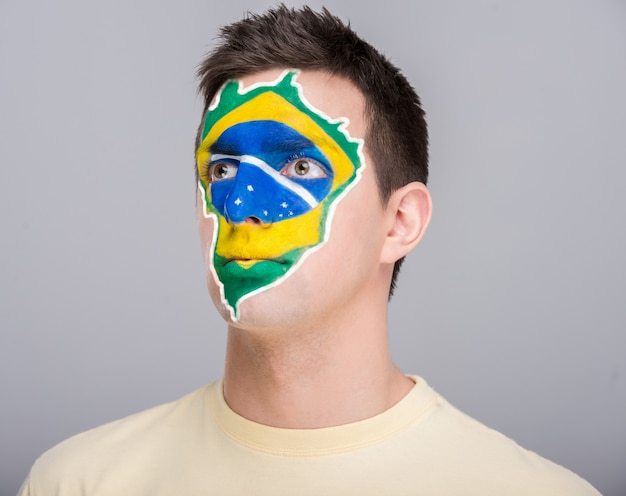Young man with brazilian flag painted on his face. Premium Photo