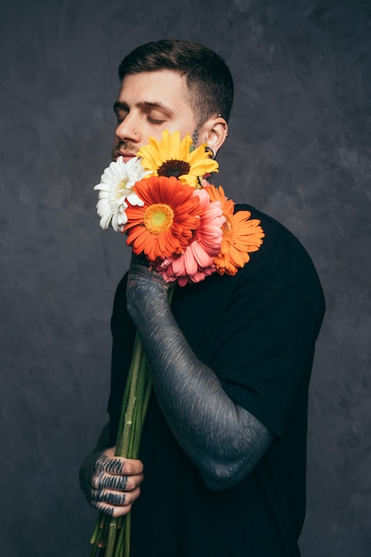 Young man with closed eyes and tattooed on his hand holding gerbera flower in hand Free Photo