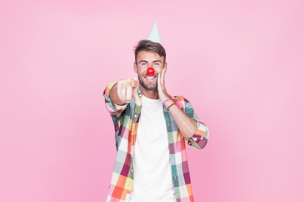 Young man with clown nose pointing his finger on pink background Free Photo