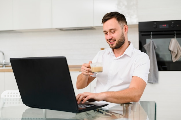Young man with coffee smiling at laptop Free Photo