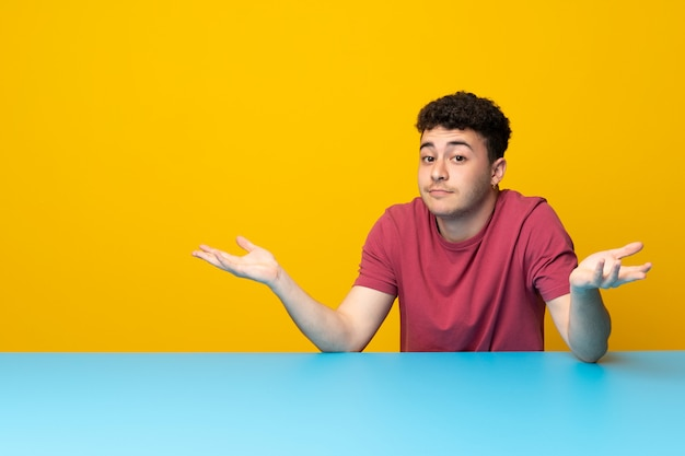 Young man with colorful wall and table having doubts while raising hands Premium Photo