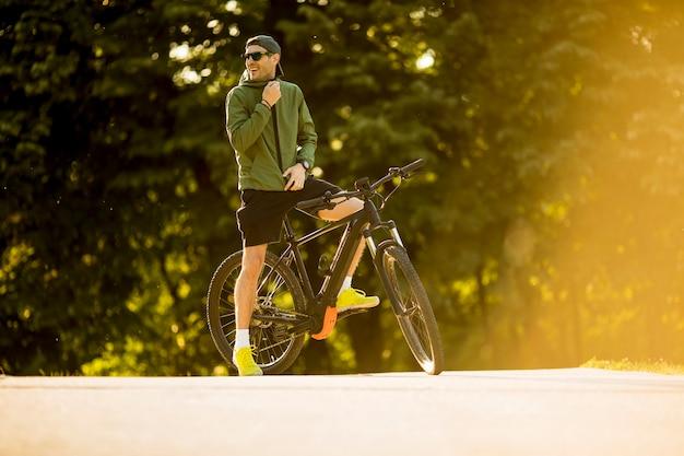 自転車、公園でバッテリー付きマウンテンバイクと若い男 Premium写真