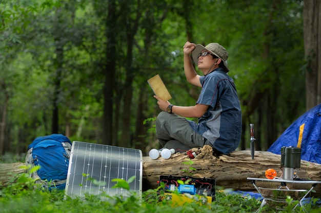 Young man with equipment for camping  and solar power box Premium Photo