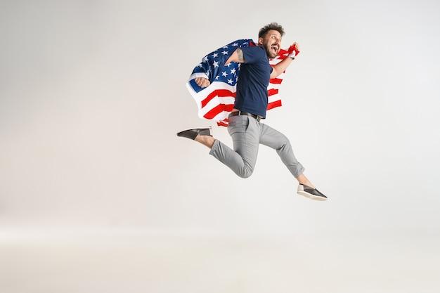Giovane con la bandiera degli stati uniti d'america che salta isolato su studio bianco. Foto Gratuite