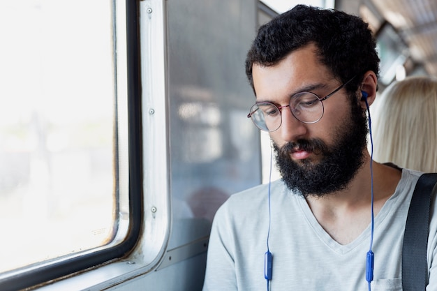 Young man with glasses, headphones and a beard sits in a train car and listens to music. tourism and travel. close-up. Premium Photo