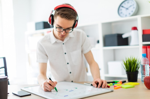 A young man with glasses and headphones draws a marker on the magnetic board. Premium Photo