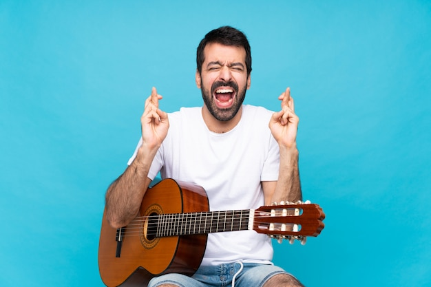 Young man with guitar over blue with fingers crossing Premium Photo