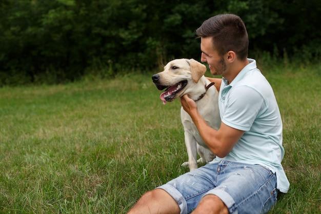 Молодой человек со счастливым лабрадором в парке Premium Фотографии