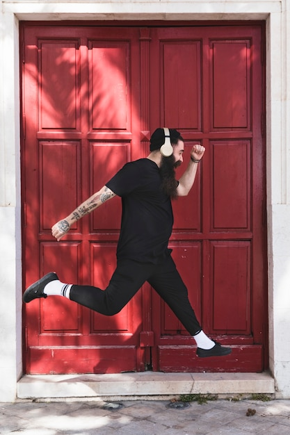 Young man with headphone on his head jumping against closed red door Free Photo