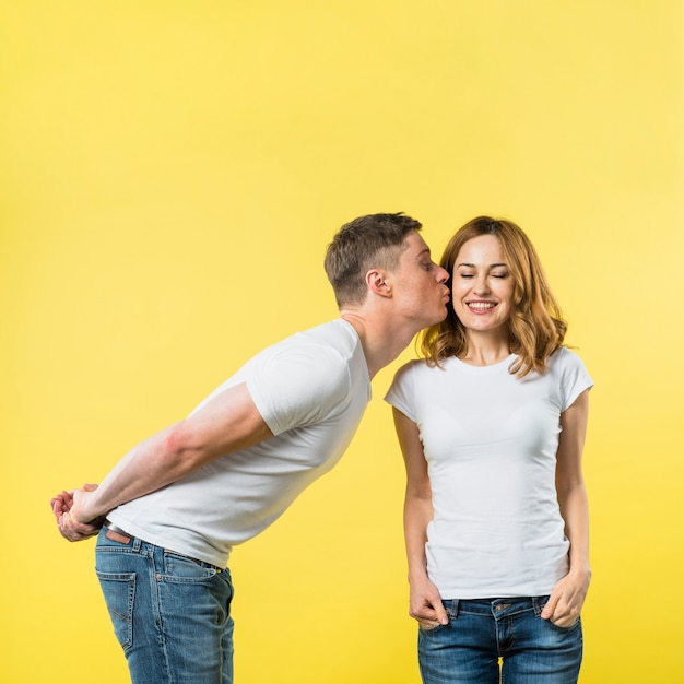 Young man with his hands at back kissing her smiling girlfriend against yellow backdrop Free Photo