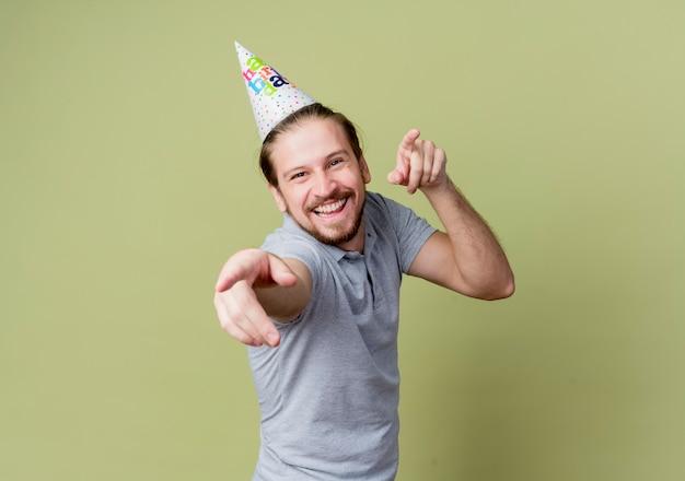 誕生日パーティーを祝うホリデーキャップを持つ若い男は、光に幸せで興奮しています 無料写真