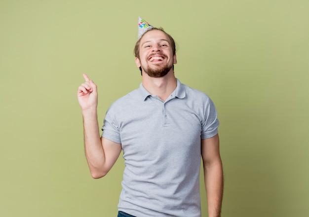 誕生日パーティーを祝うホリデーキャップを持つ若い男は、光の壁に人差し指を見せて幸せで興奮しています 無料写真