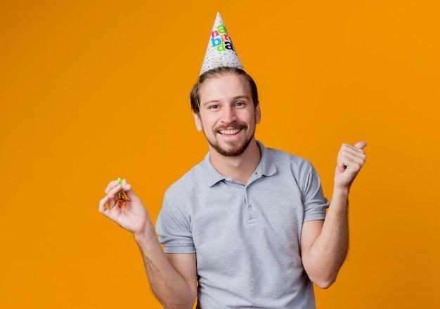オレンジ色の壁の上に立って幸せで興奮した笑顔の誕生日パーティーを祝うホリデーキャップを持つ若い男 無料写真