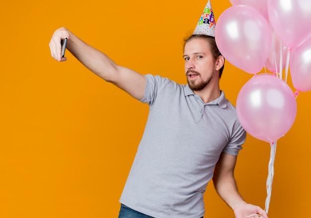 オレンジ色の壁の上に立っているスマートフォンを使用してselfieを行う風船の束を保持している誕生日パーティーを祝うホリデーキャップを持つ若い男 無料写真