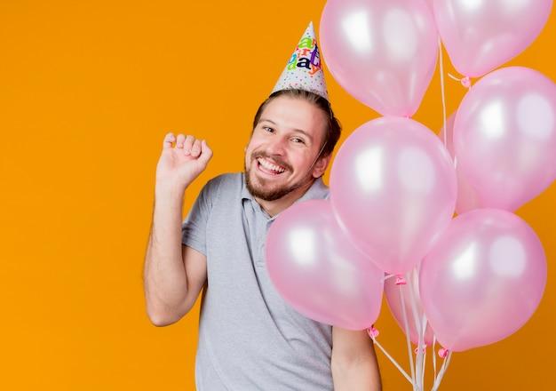 オレンジ色の壁の上に元気に立って幸せで興奮した笑顔の風船の束を保持している誕生日パーティーを祝うホリデーキャップを持つ若い男 無料写真