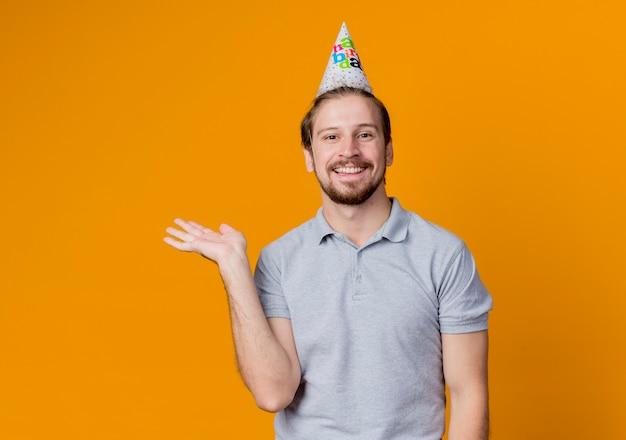 オレンジ色の壁の上に広く立って幸せで陽気な笑顔で何かを提示する誕生日パーティーを祝う休日の帽子を持つ若い男 無料写真