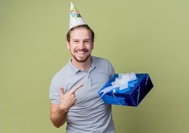 誕生日プレゼントを持ってホリデーキャップを持つ若い男は、光の壁に幸せで興奮して誕生日パーティーを祝って笑っています 無料写真