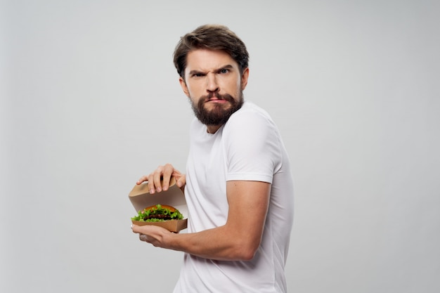 Young man with a juicy hamburger in his hands, a man eating a burger Premium Photo