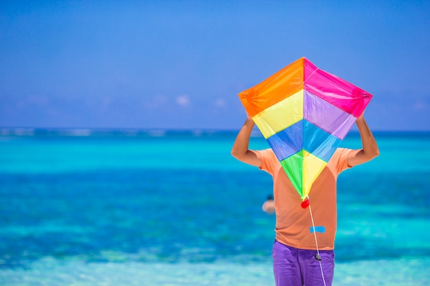 Young man with a kite on a background of turquoise sea Premium Photo