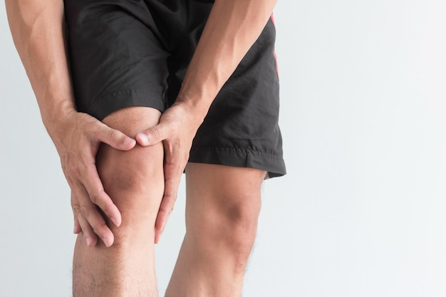 Young man with knee pain and copy space Premium Photo