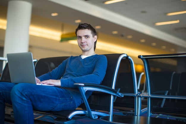 Young man with laptop at the airport while waiting his flight Premium Photo