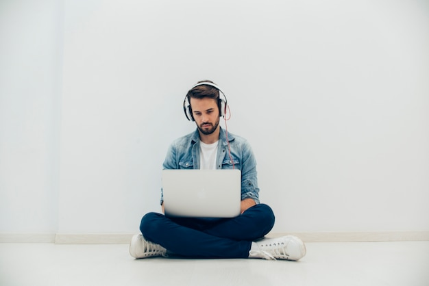 Young Man With Laptop Sitting On The Floor