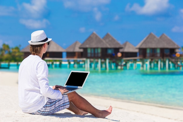 Young man with laptop at tropical beach near water villa Premium Photo