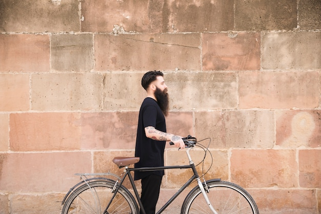 Young man with long bearded man standing with bicycle against wall Free Photo