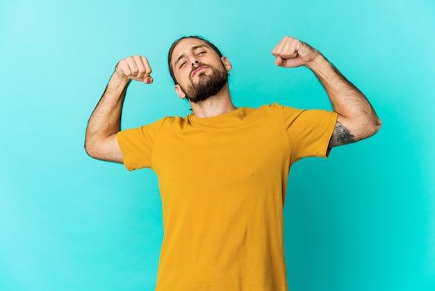 Молодой человек с длинными волосами смотрит, показывая жест силы руками, символ власти Premium Фотографии