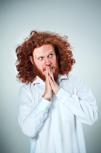 Il giovane dai lunghi capelli rossi che guarda da parte nel pensiero Foto Gratuite