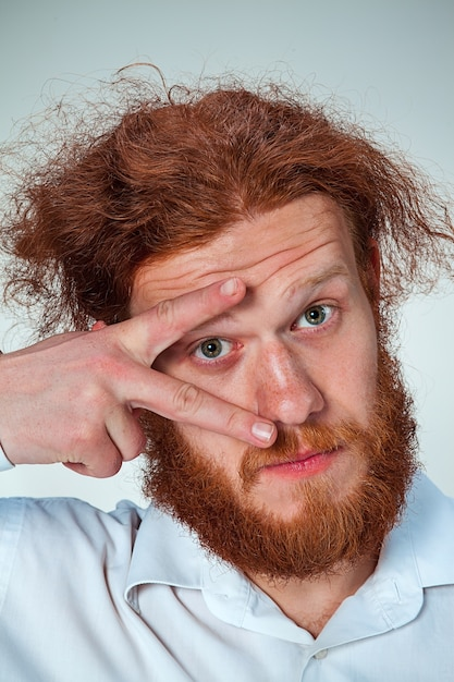 Il giovane con lunghi capelli rossi che guarda l'obbiettivo, aprendo gli occhi Foto Gratuite