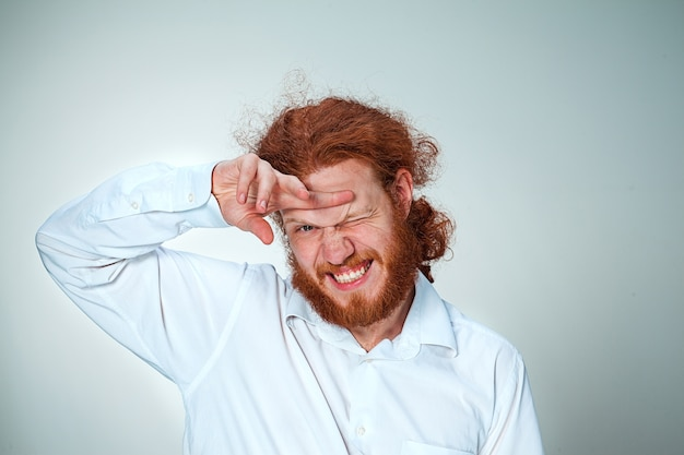 Il giovane con lunghi capelli rossi che guarda l'obbiettivo, strizzando gli occhi Foto Gratuite