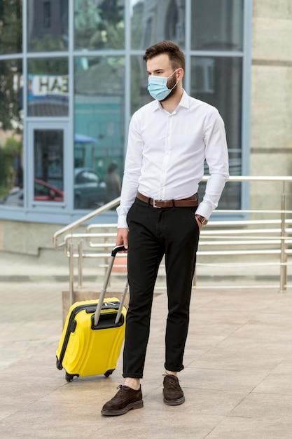 Giovane con bagagli che indossa la maschera Foto Gratuite