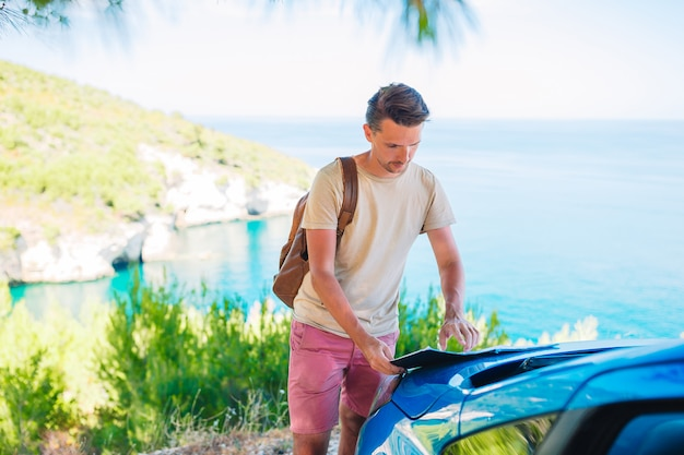 Young man with map travel by car on summer vacation Premium Photo