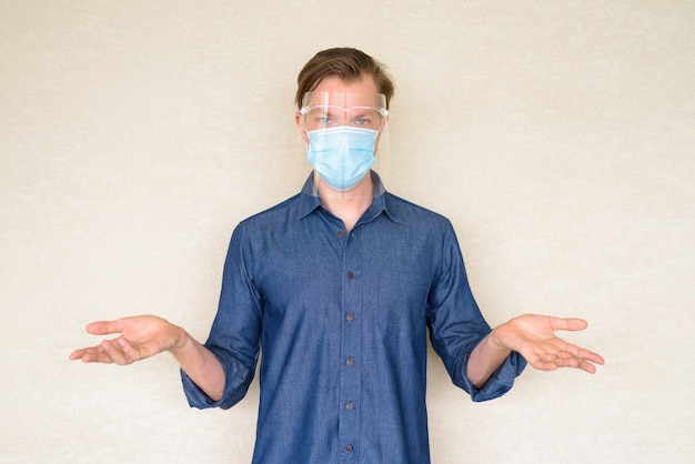 コンクリートの壁に肩をすくめマスクと顔のシールドを持つ若者 Premium写真