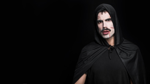 Young man with pale face and scars posing in halloween costume Free Photo