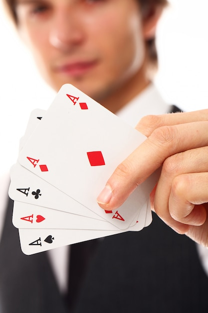 Young man with poker cards, close up Free Photo